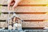 Investissement dans l'immobilier neuf à Nantes et dans sa région - Main qui insère des pièces de monnaie dans une tirelire en forme de maison