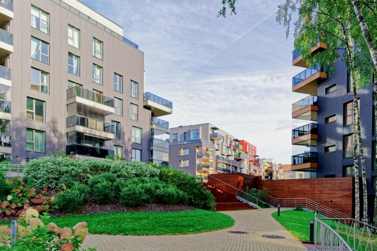 Un immeuble moderne donnant sur une place avec de la verdure