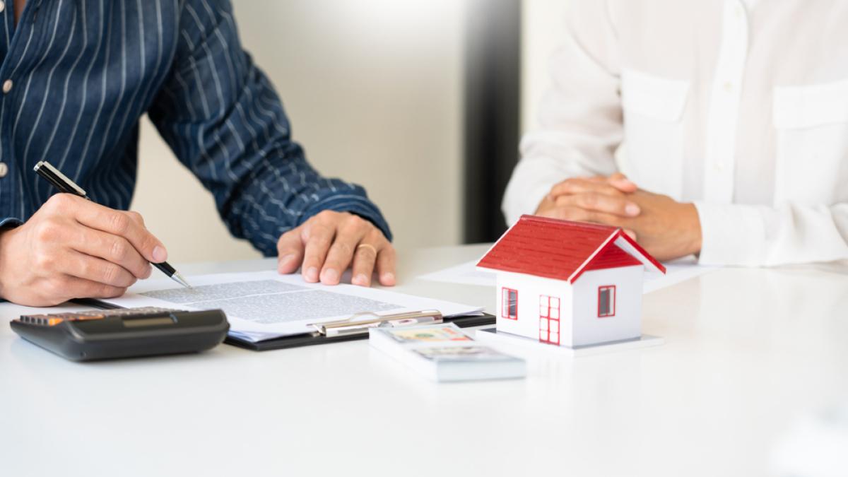 Avantages de l'immobilier neuf - Les agents immobiliers expliquent le document aux clients qui viennent s'adresser pour acheter une maison