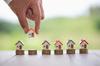 Loi Girardin – La main de la femme qui met le modèle de maison sur la pile de pièces. Concept d'échelle immobilière