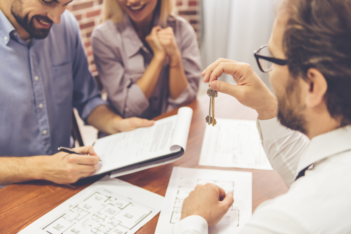 Location à Nantes – Jeune couple signant son contrat de location et agent immobilier leur tendant les clés