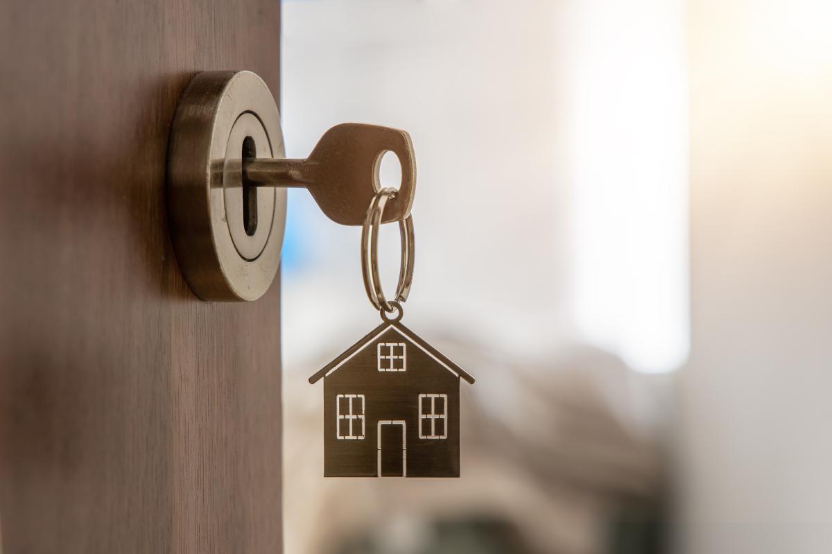 Logement étudiant à Nantes – Clé avec un porte-clé en forme de maison sur une porte ouverte